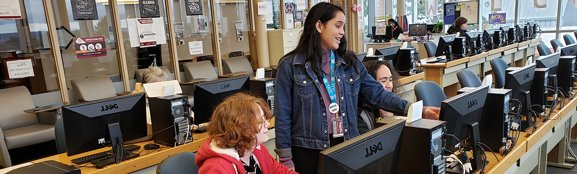computer lab employee assisting two students at computers