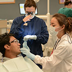 student in robes and face masks working on dental patient